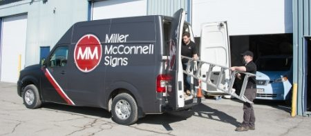 Miller McConnell staff members packing up sign installation equipment